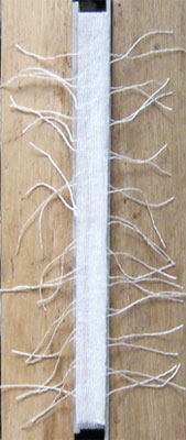 A layer of scrim covers the  threads.